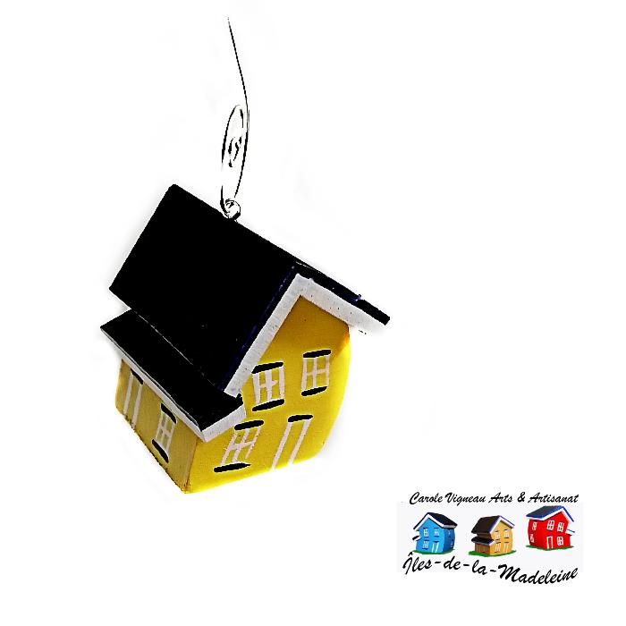 . Une coquette petite maison jaune légèrement inclinée pour représenter le vent des Îles-de-la-Madeleine.
