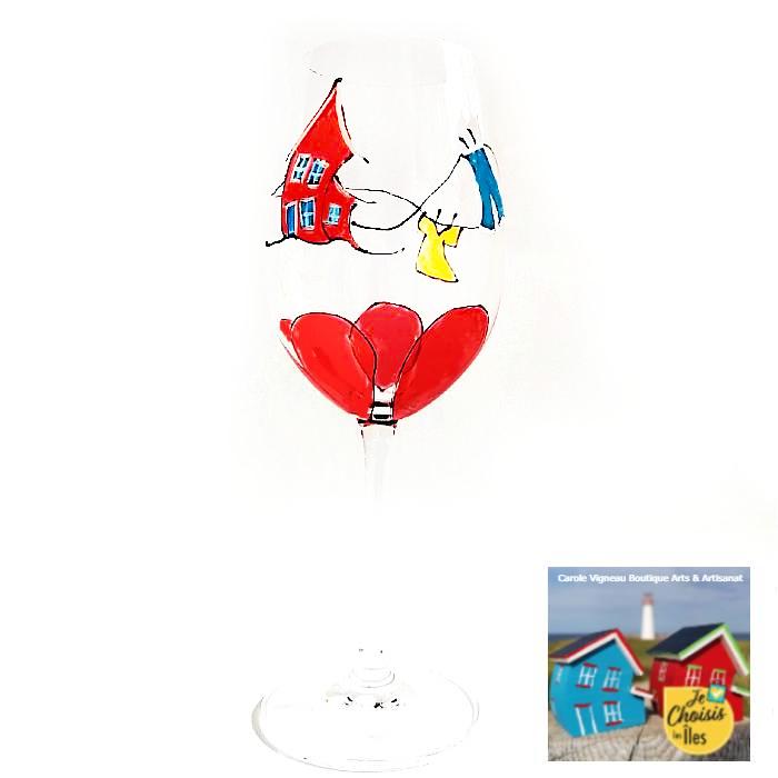 Un verre à vin blanc habillé d'une belle fleur rouge avec maison croche inspirée par le vent des Îles-de-la-Madeleine peinte à la main. Enrobée de la corde à linge dansante.  La soif des Îles gravée sur le pied